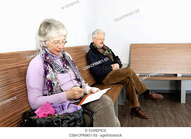 Elderly woman listening to a mobile mp3 player with ear phones in and an envelope in her hand in a general medical practice waiting room