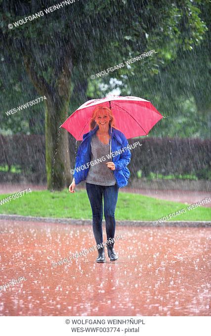 Austria, Thalgau, teenage girl with red umbrella walking in the rain