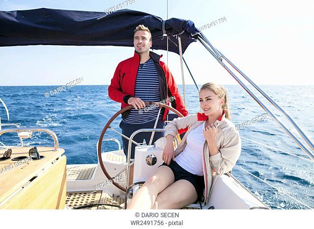 Man at steering wheel of sail ship