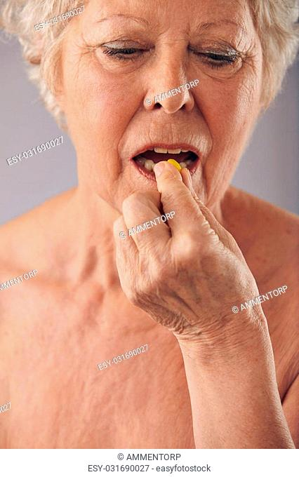 Close-up image of a senior woman taking a pill against grey background. Old female taking medicine