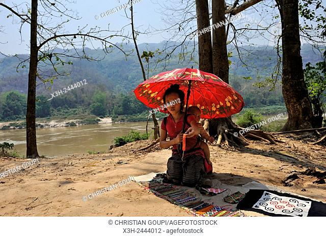little girl showing clothes and local crafts for sale to tourists passing through Ban Baw, a traditional Lao Loum village by the Mekong River
