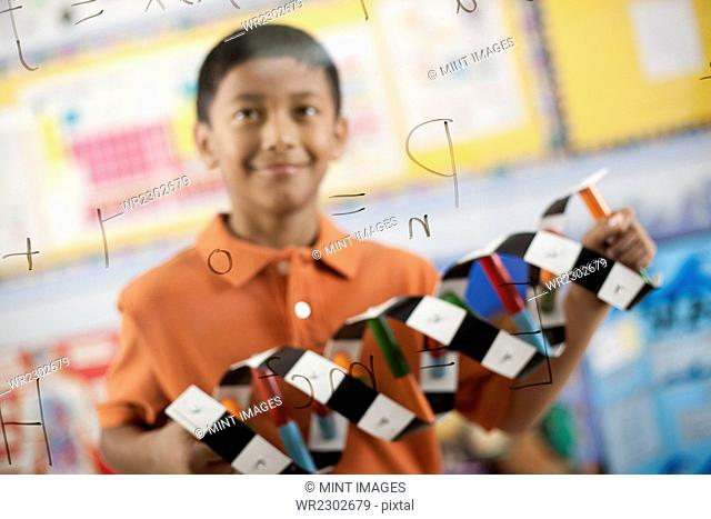 A boy looking at a board with written scientific equations and calculations, holding a molecular structure model, a double helix in his hands