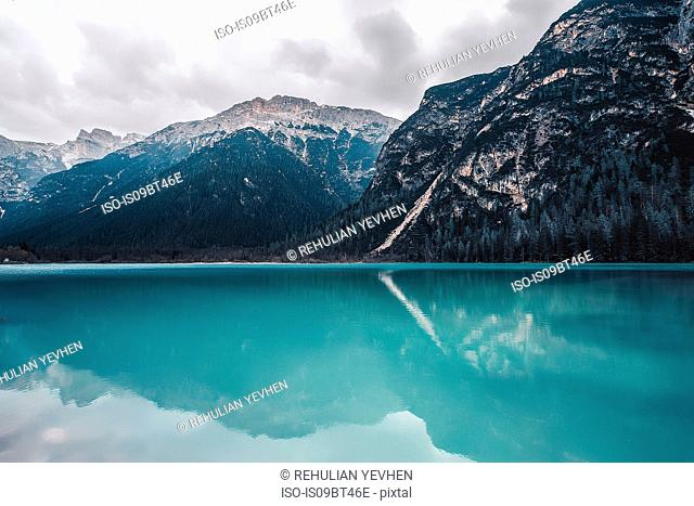 Landscape with turquoise lake and snow capped mountains, Dolomites, Italy