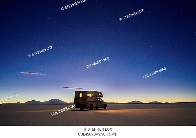 Recreational vehicle, travelling at dusk, across salt flats, Salar de Uyuni, Uyuni, Oruro, Bolivia, South America