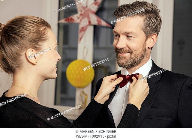 Couple preparing for New Year's Eve party, fastening bow tie