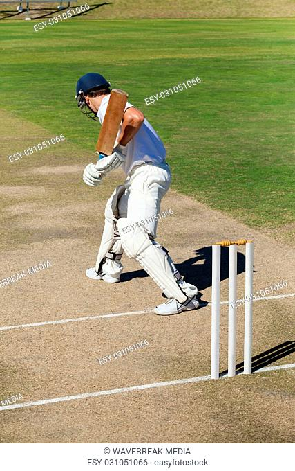 Side view of cricket player practicing on field