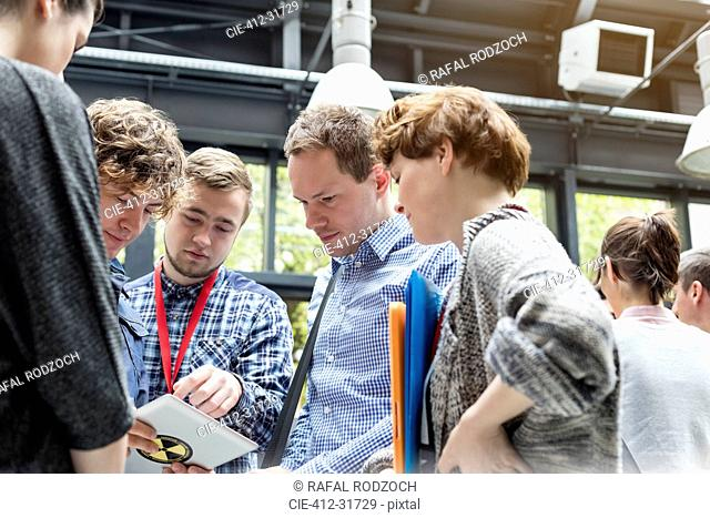 Business people using digital tablet at technology conference