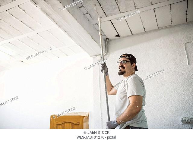 Smiling man painting ceiling of a garage