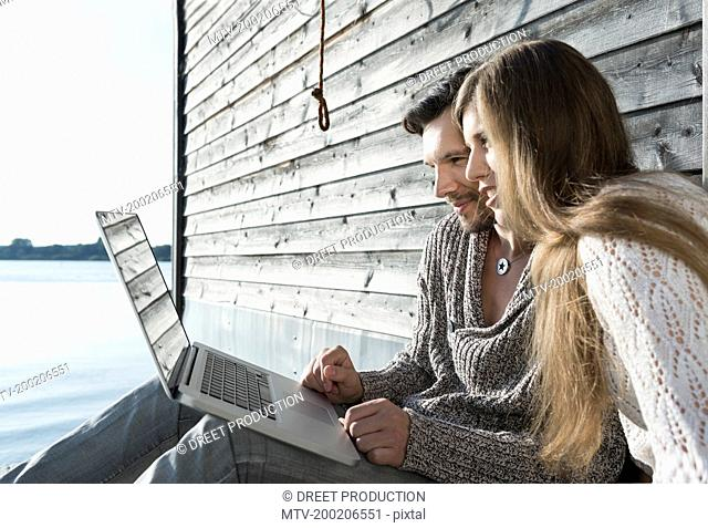 Man woman using laptop computer outdoors