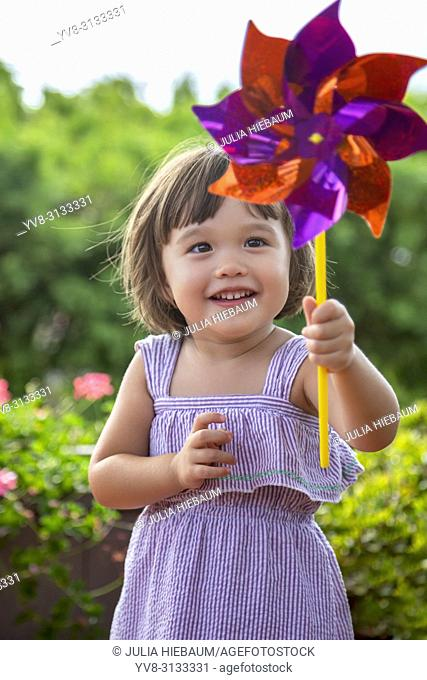 Two year old girl holding a pinwheel