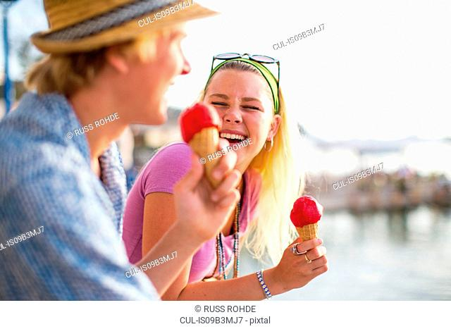 Young couple laughing and eating ice cream cones on waterfront, Majorca, Spain