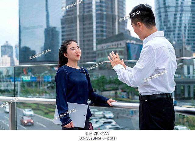 Young businesswoman and man talking on balcony in city financial district, Shanghai, China