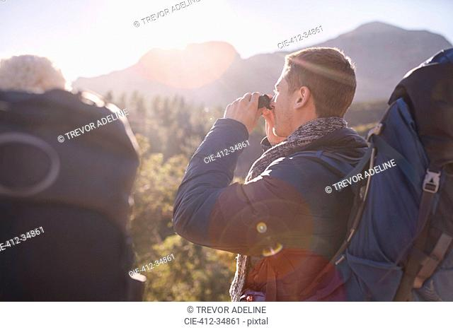 Young man with backpack hiking using binoculars in sunny field