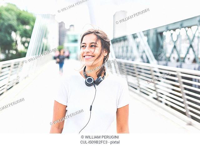 Young woman standing on bridge, headphones around neck, smiling