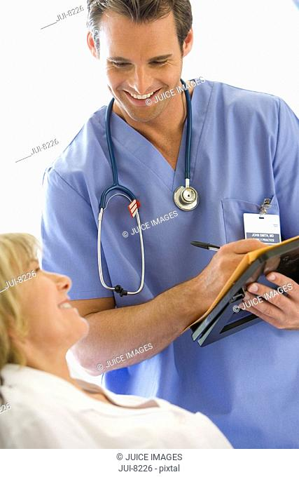 Young male nurse writing in file by mature female patient, smiling, close-up