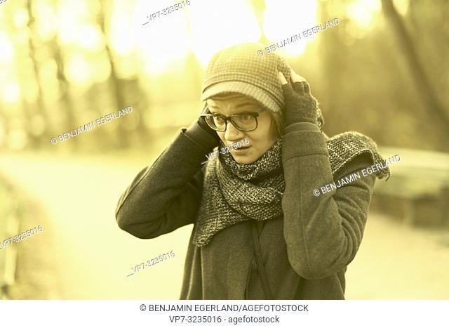 woman in park, head between hands, in Munich, Germany