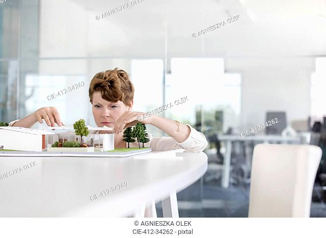 Focused female architect arranging model in conference room