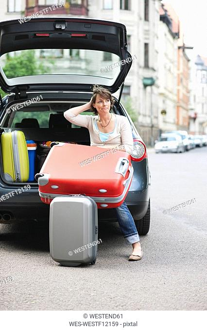 Germany, Leipzig, Woman sitting at back of car, holding suitcase