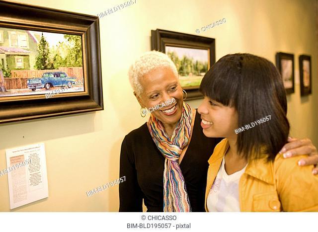 Grandmother and granddaughter hugging in gallery