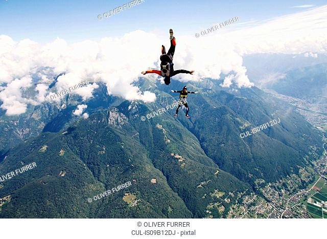 Freestyle skydiving team training together. One man performing air-ballet, another jumper is filming with video camera on helmet, Locarno, Tessin, Switzerland