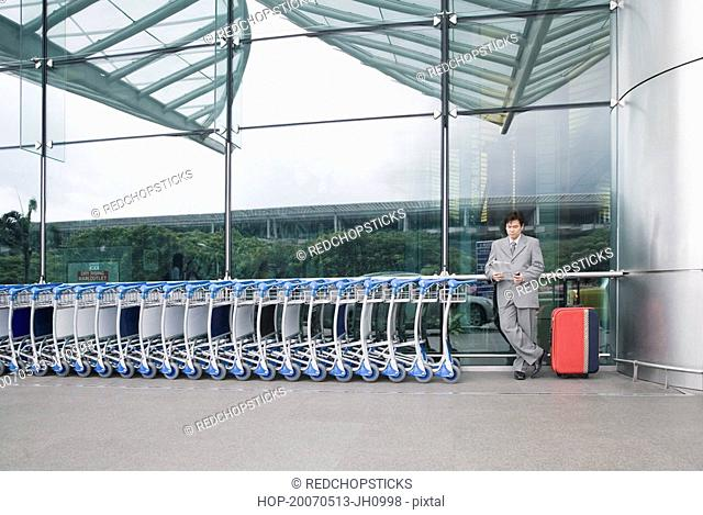 Businessman reading a document and waiting outside an airport