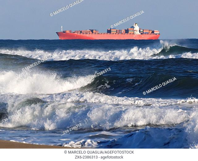 Container ship near seashore of Prat de Llobregat city on a windy afternoon. Barcelona Metropolitan Area, Catalonia, Spain