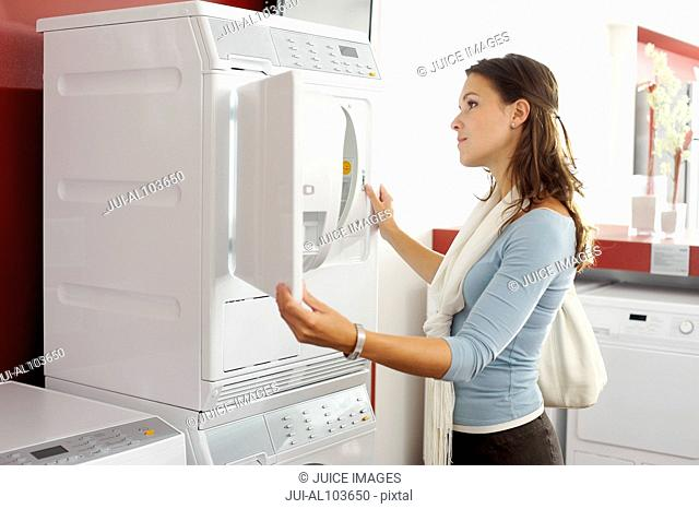 A woman looking at a washing machine in an electrical shop