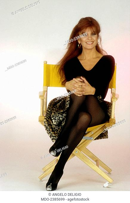 Italian singer and actress Milva (Maria Ilva Biolcati) posing smiling on a foldable chair with crossed legs. 1984