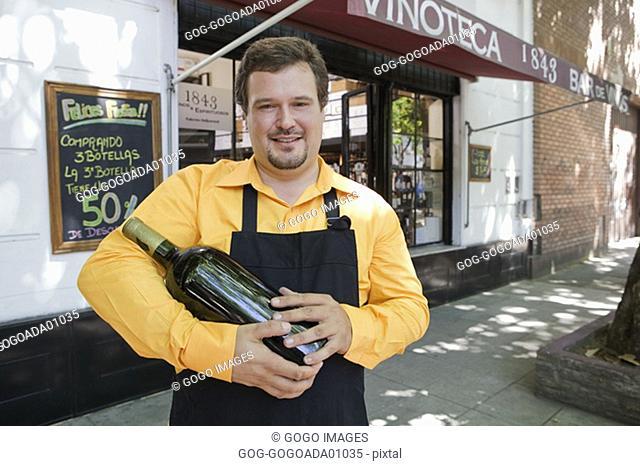 Male employee holding wine bottle outside store