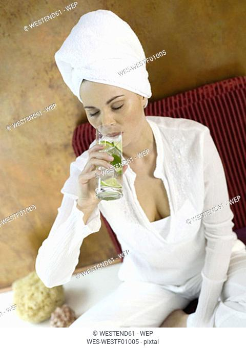 Woman sitting on cushion, drinking lime water, close-up