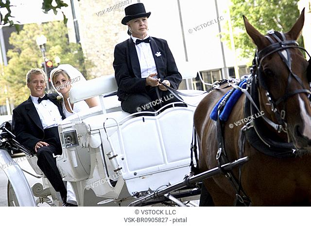 Bride and groom on horse drawn carriage ride