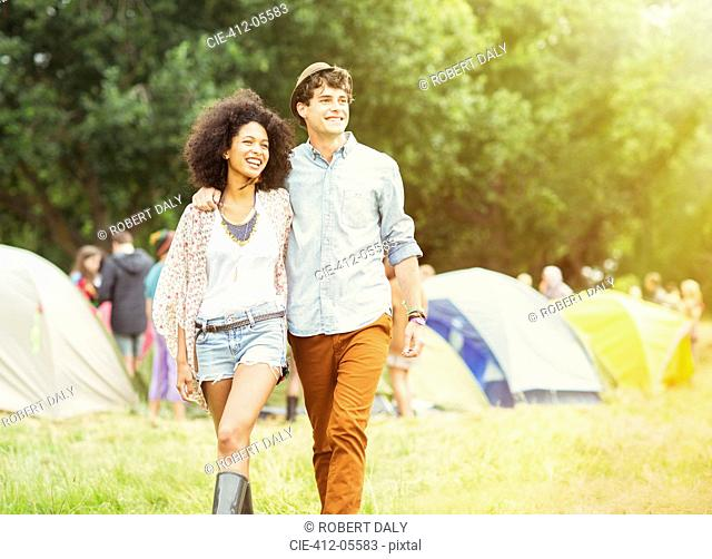 Couple walking outside tents at music festival