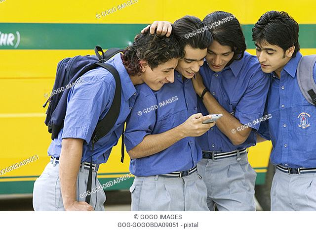 Male students crowding around cell phone
