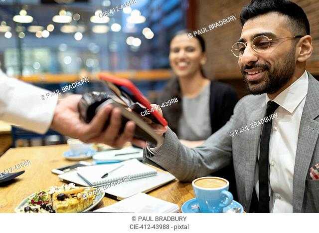 Businessman paying with smart phone contactless payment in cafe