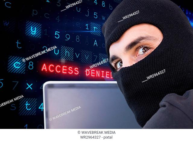 Cyber criminal wearing a hood uses a laptop against website code background
