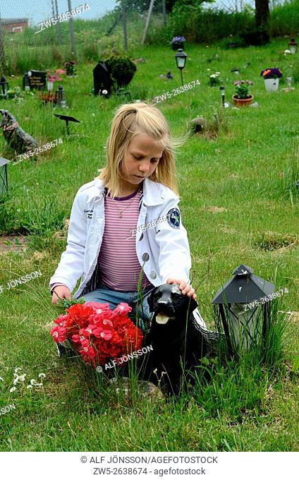Little girl at her pet's grave in Ystad, Sweden