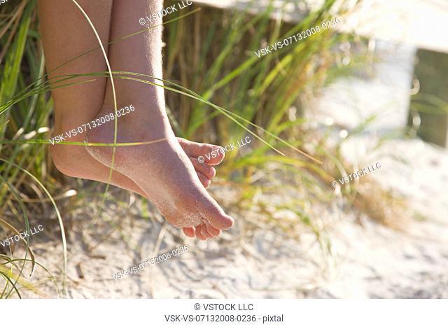 USA, Florida, St. Pete Beach, Bare feet of girl 8-9 sitting on rail on beach