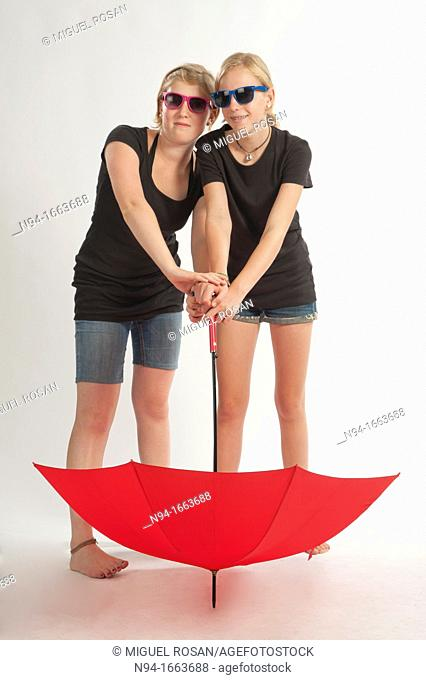 Two young German girls playing with an umbrella