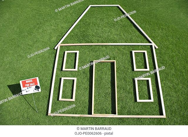 """""""For sale"""" sign and house outline in grass"""