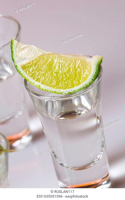 Tequila in glass with lime on white background
