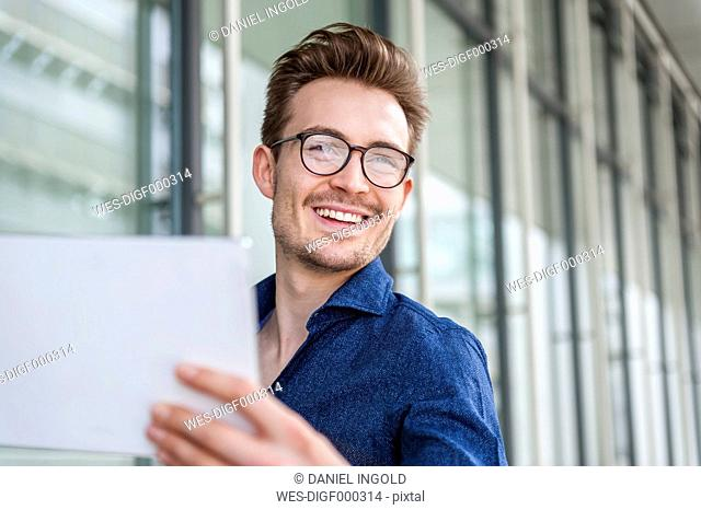 Portrait of smiling young businessman with digital tablet