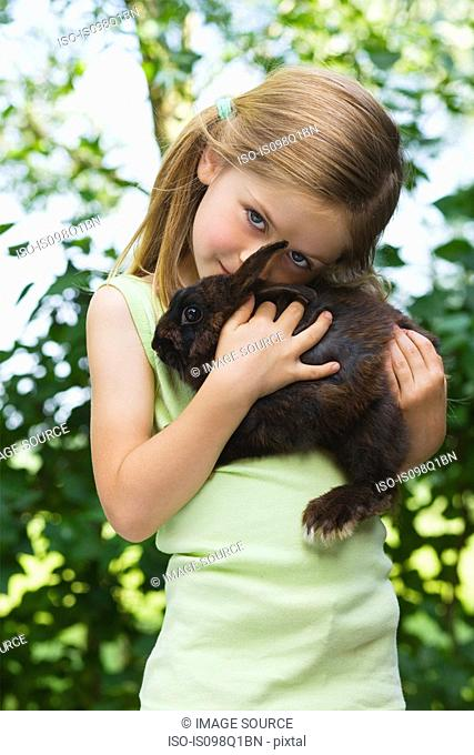 Portrait of a girl holding a rabbit