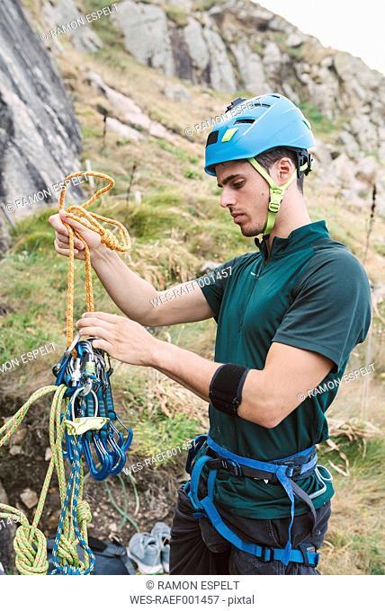 Young man preparing climbing equipment