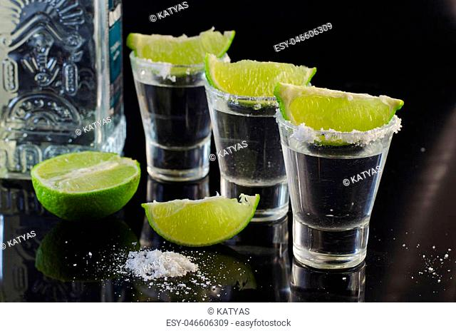 Silver tequila with lime and salt on a black table