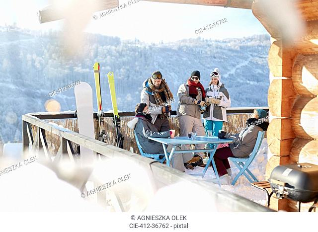 Skier and snowboarder couples hanging out on sunny cabin balcony apres-ski