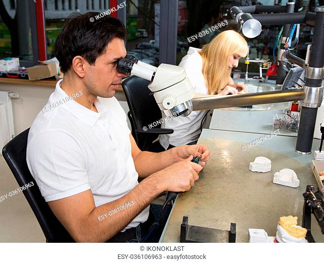 Two dental technicians at their workplace polishing dental prosthesis