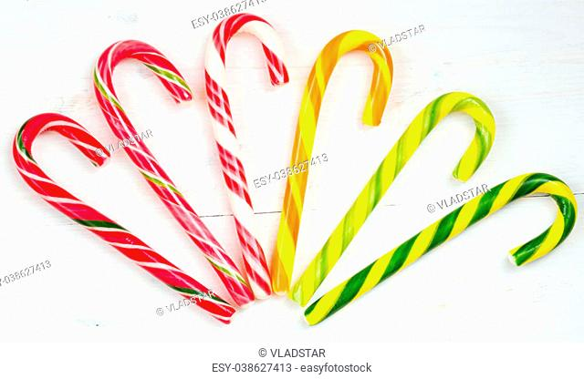 Christmas candy cane on the white wooden background