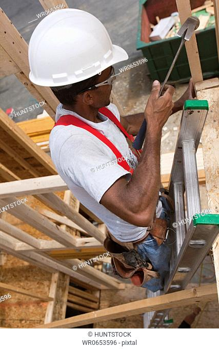 Hispanic carpenter using a hammer on a ladder at a house under construction