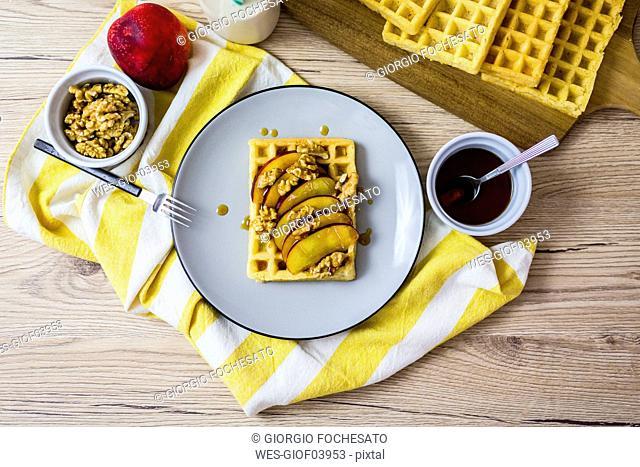 Waffle garnished with nectarine, walnuts and maple sirup