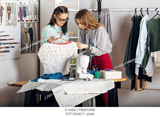 Trainee examining dress's fabric by designer holding coathanger at fashion studio